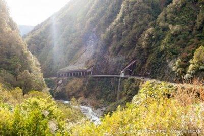 Straße am Berghang mit Geröllschutz und Wasserbrücke