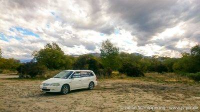 Minivan auf sandigem Platz in der Natur