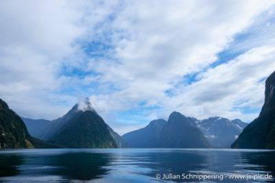 blaues Wasser mit hohen Bergen im Hintergrund