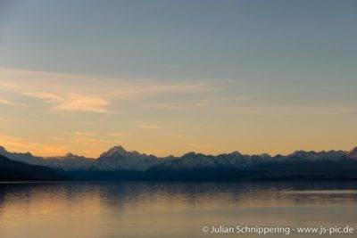 spiegelglatter See und Berge mit Schnee am Horizont