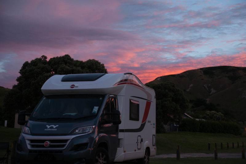 Ein größerer Camper steht vor grüner Kulisse am Sonnenuntergang