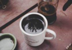 Kaffee Tasse mit French Press Kanne im Hintergrund