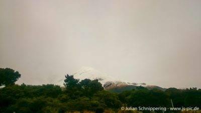 Schneebedeckter Gipfel von Mt. Taranaki umgeben von Regenwolken