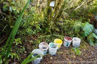 Eimer mit Schotter gefüllt vor grünen Bäumen