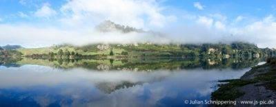 spiegelglattes Wasser und Nebelverhangene Berge