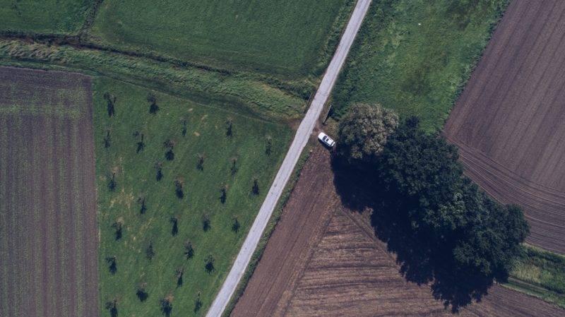 Sicht aus der Vogelperspektive auf eine Straße und die umliegenden grünen Wiesen
