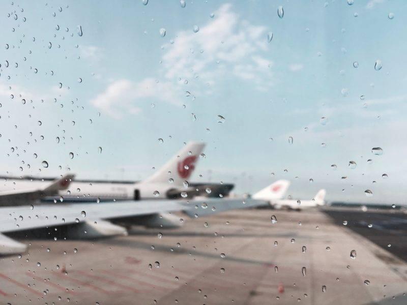 Blick durch eine Scheibe mit Regentropfen in Richtung mehrerer Flugzeuge