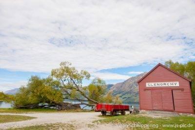 alte Hütte in rot mit einem Eisenbahnwaggon davor