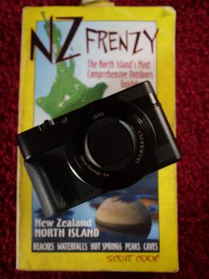 Kompakte Kamera liegt auf einem Neuseeland Reiseführer