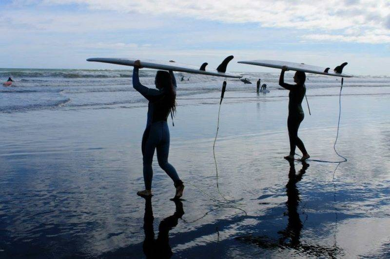 2 junge Damen tragen ihre Surfbretter auf dem Kopf in Richtung Wasser