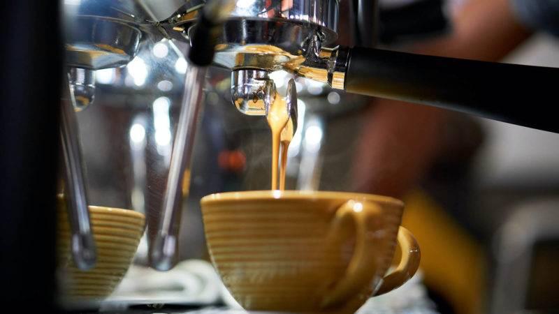 Tasse unter einer Siebträgerkaffeemaschine in einem Cafe
