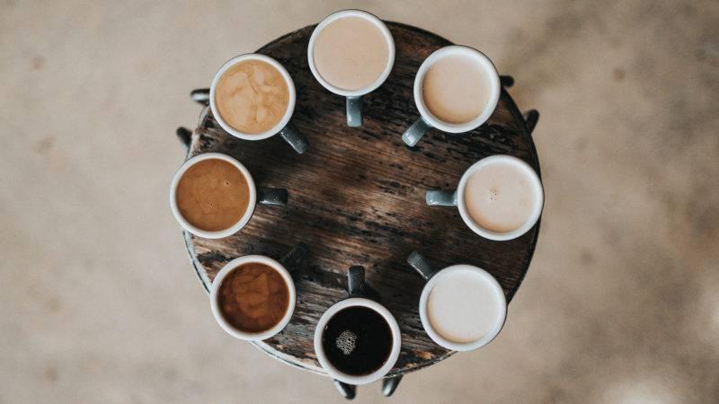Verschiedene Kaffee Spezialitäten auf einem runden Holztisch